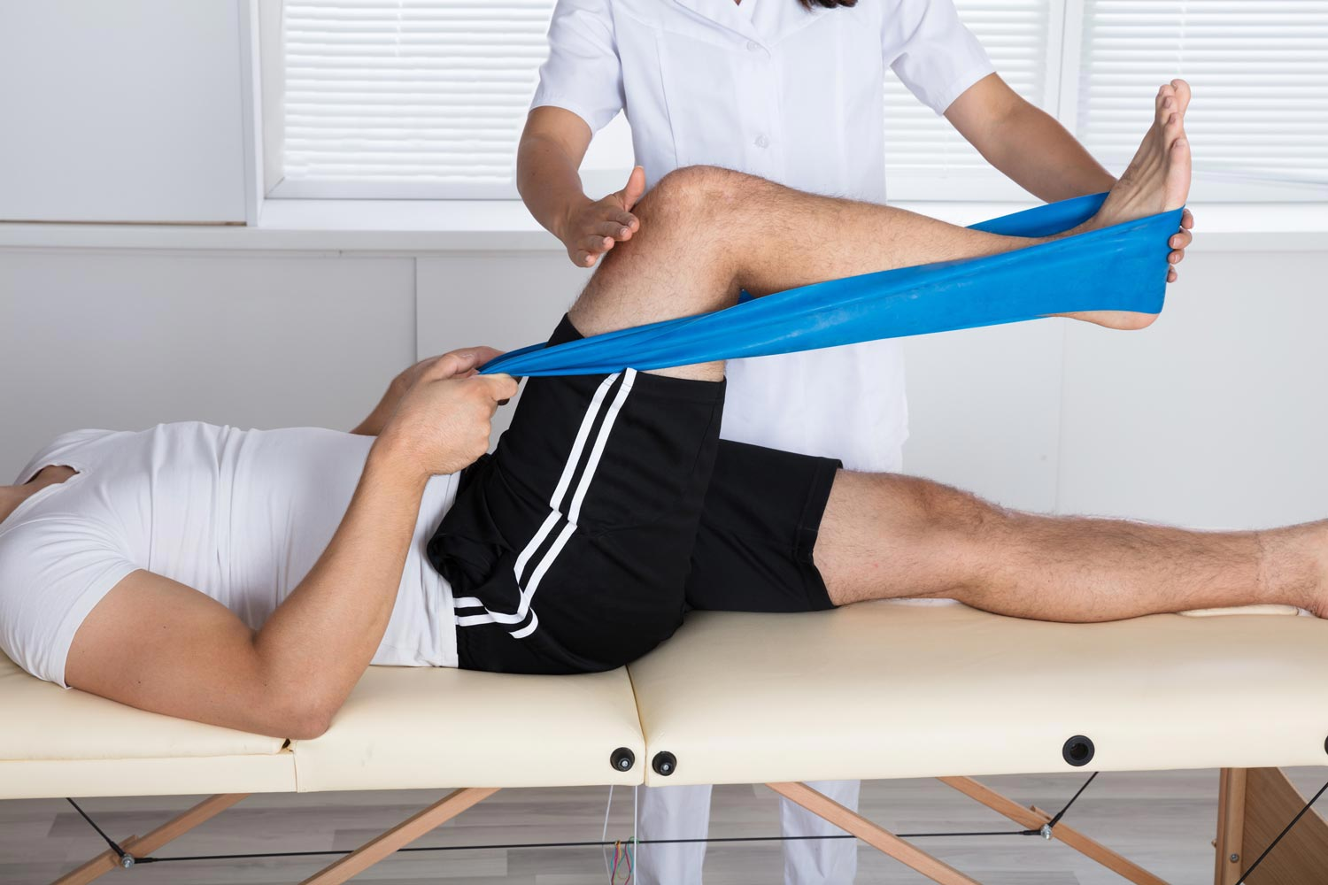 Physical therapy session, stretching out leg muscles